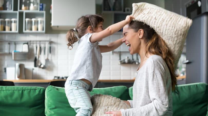 Bebé niño niñera jugando en la sala de estar almohada pelea mamá