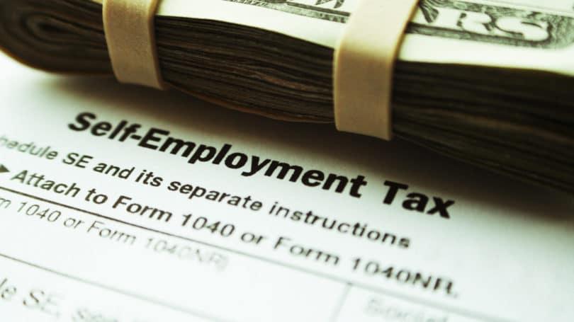 Facturas de dólares de impuestos de trabajo por cuenta propia apiladas