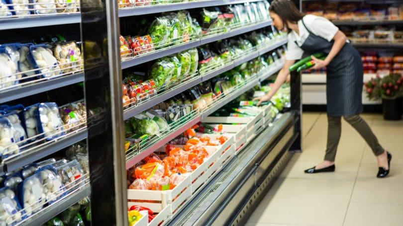 Mujer empleada de tienda almacenando comestibles producir